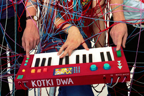 Kotki Dwa tied to their cardboard keyboard